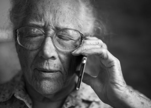 old lady wearing glasses with phone next to face