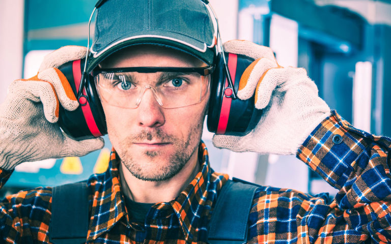 man wearing earmuffs, safety glasses and a hat