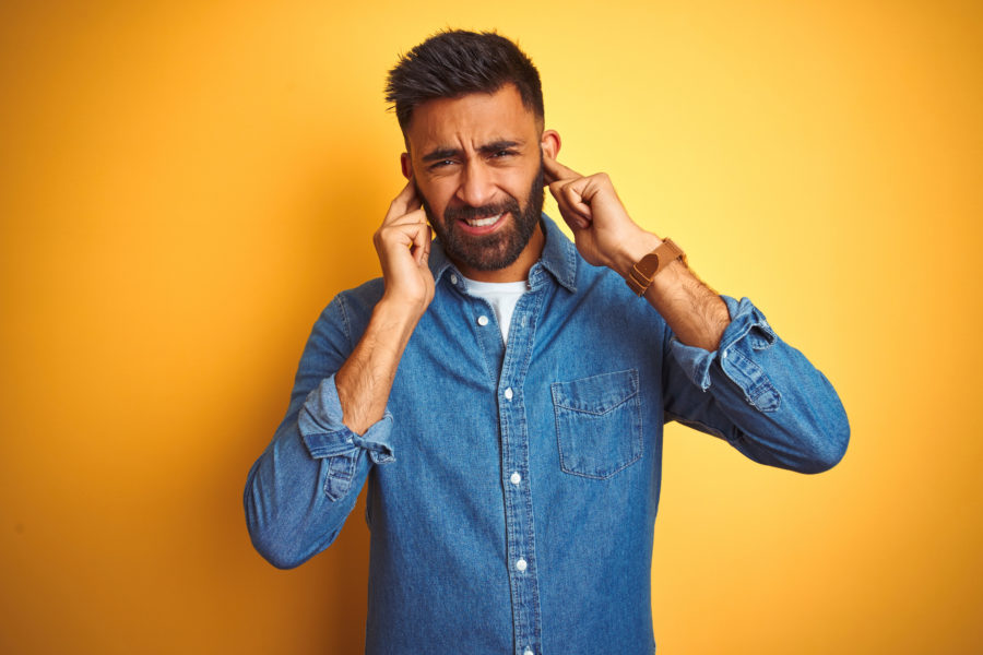 man with ear pain or tinnitus in ears