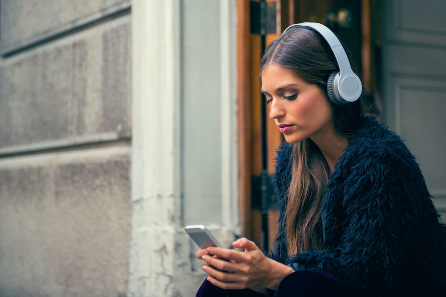 woman wearing white headphones and using a phone