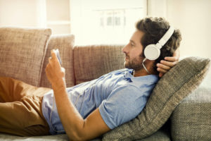 man using white headphones and watching video on mobile phone