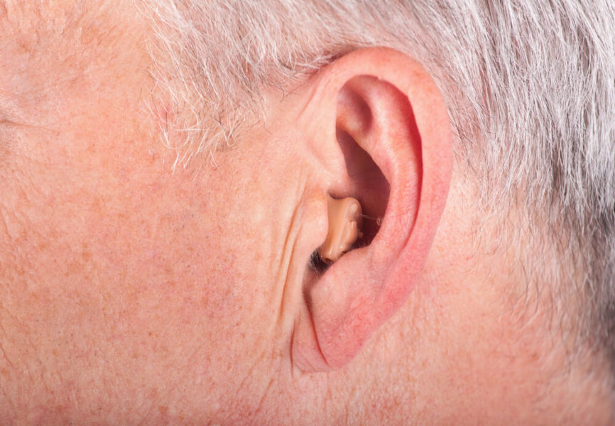 invisible hearing aid in man's ear